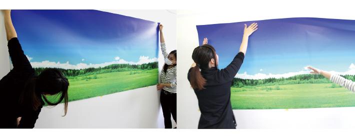 2人でしっかりとピンと張りながらフリース壁紙を貼ります